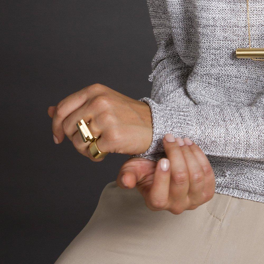 תמונה על דוגמנית, טבעת בצבע זהב מבריק, עם שני מלבנים בגדלים שונים לרוחב.