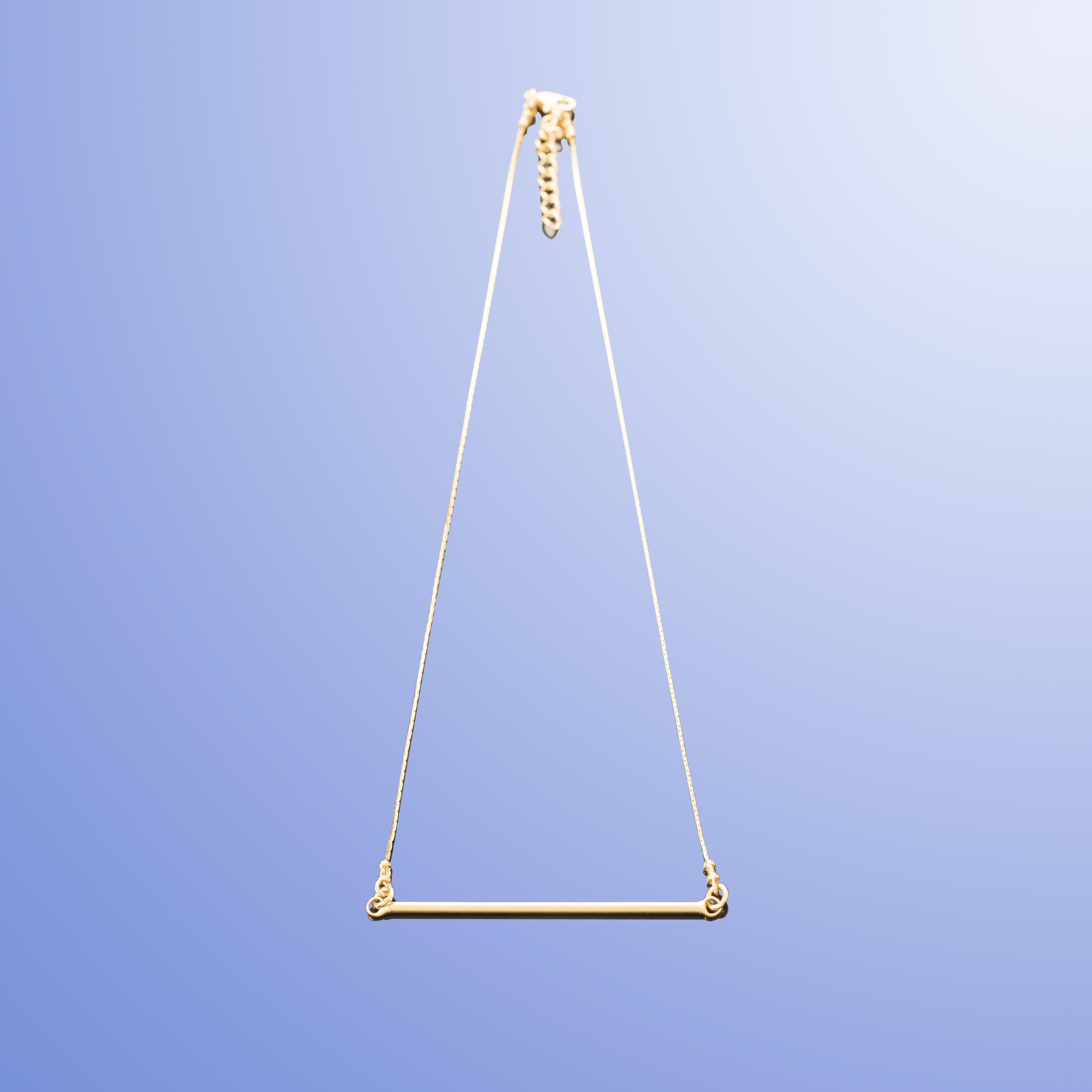תמונת מוצר, שרשרת עדינה בצבע זהב, עם תליון בצורת מוט דק מאוזן.