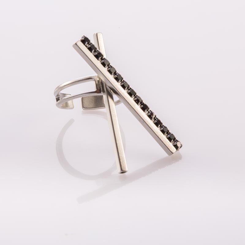 תמונת מוצר, טבעת בצבע כסף עם שני מוטות ארוכים מולחמים באיקס כשאחד מהם משובץ אבנים שחורות קטנות לכל אורכו.