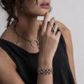 תמונה על דוגמנית, שרשרת גורמטים עדינים בצבע כסף עם תליון סוגר טי גדול, וטבעת בצבע כסף עם שני מקלות ארוכים מולחמים באלכסון.