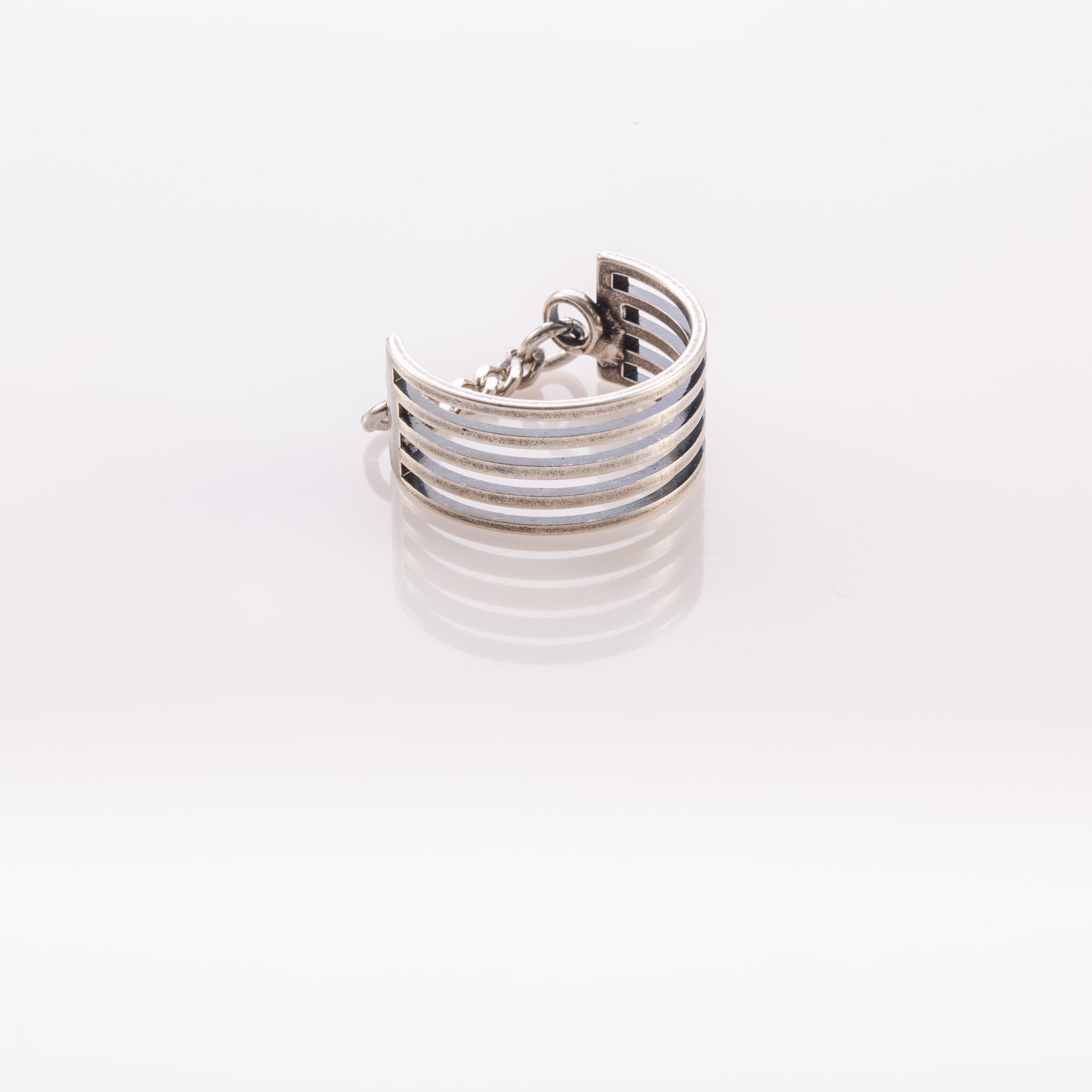 טבעת רחבה בצבע כסף הבנויה מפסי מתכת דקים ושרשרת גורמט דקה בחלק האחורי.