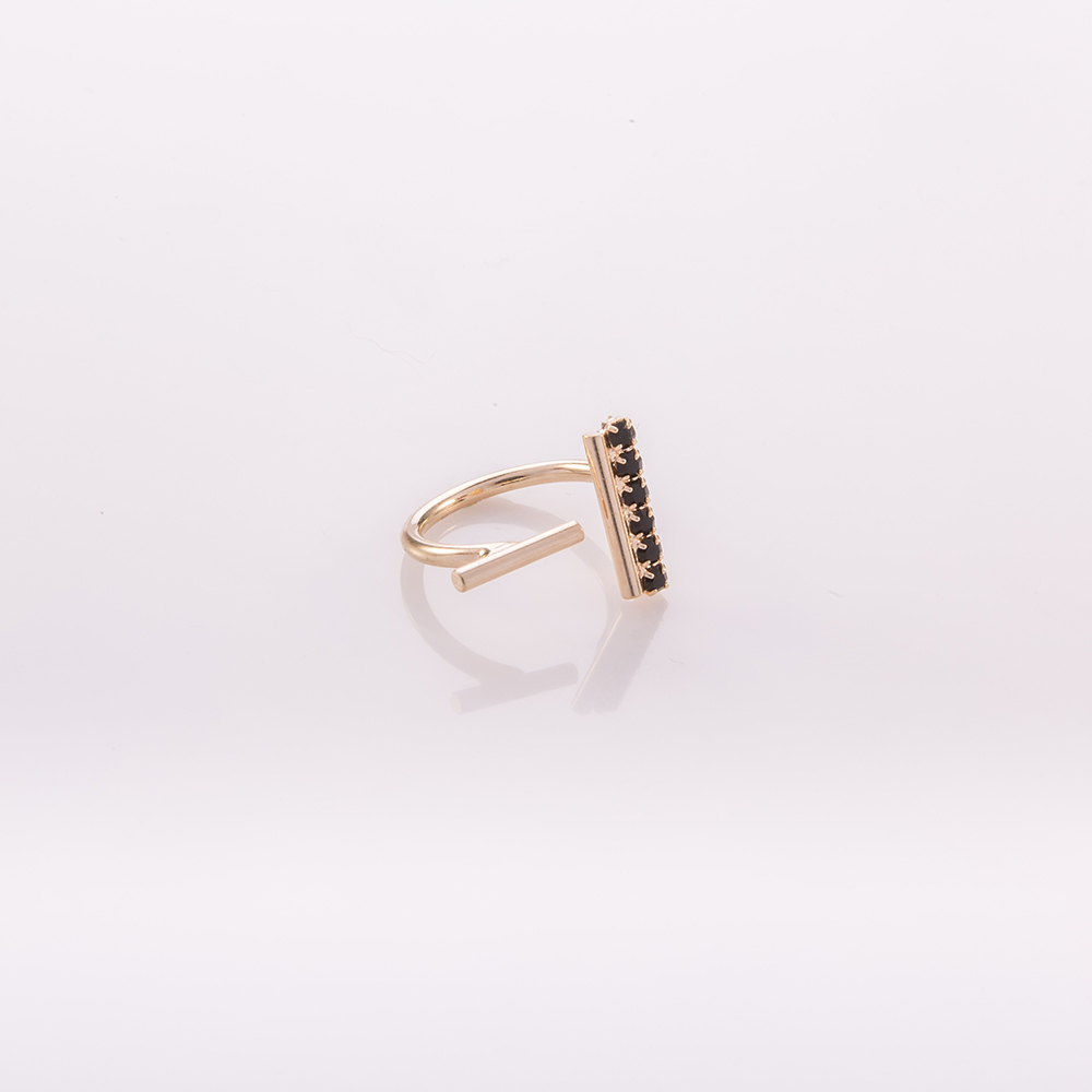 תמונת מוצר, טבעת פתוחה, בצבע זהב, בקצה אחד מוט קצר לאורך משובץ אבנים שחורות ובקצה השני מוט קצר לרוחב.