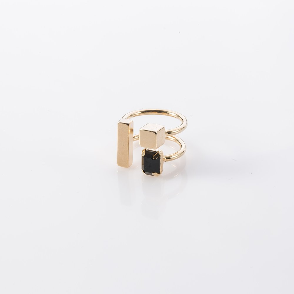 תמונת מוצר, טבעת בצבע זהב, הבנויה משני בסיסים פתוחים ועליהם מסודרת קומפוציה של צורות גאומטריות: מלבן קוביה ומלבן קטן יותר משובץ אבן שחורה.