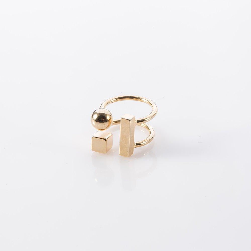 תמונת מוצר, טבעת בצבע זהב, הבנויה משני בסיסים פתוחים עליהם מסודרת קומפוזיציה של צורות גאומטריות בתלת מימד: מלבן קוביה וכדור.
