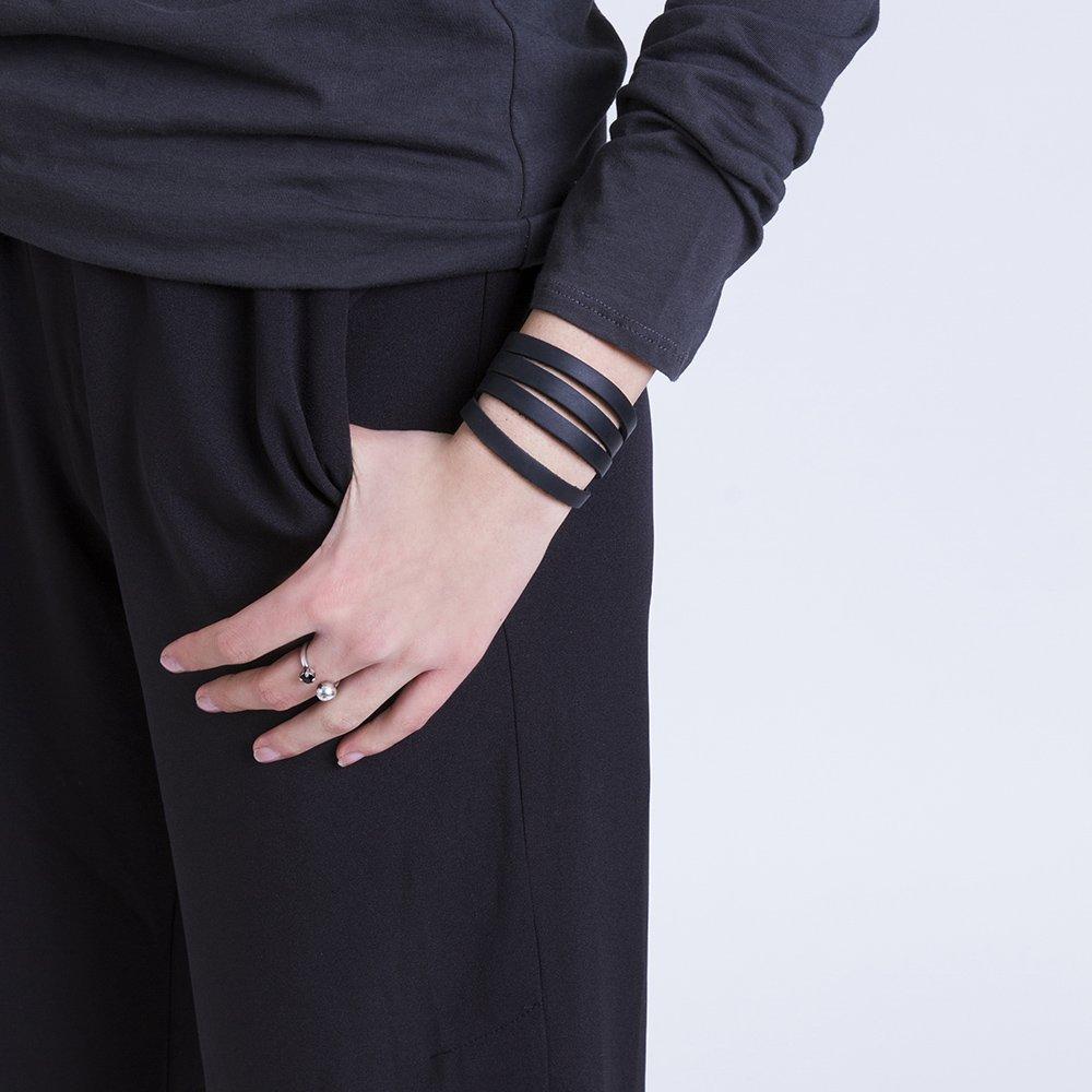 תמונה על דוגמנית, צמיג עור שחור החתוך לרצועות ויוצר מראה של כמה רצועות עור על היד.