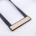 תמונת מוצר, שרשרת קצרה מרצועות עור שחורות בשילוב לוחית מתחת מלבנית בצבע זהב.