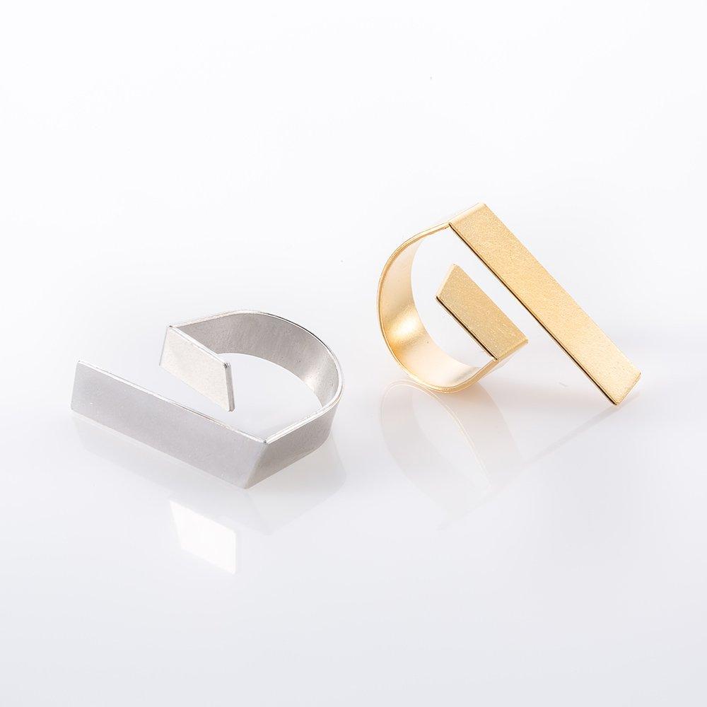 תמונת מוצר, טבעת הבנויה ממלבן שטוח מעוגל ומכופף בצורת האות ט' כאשר חלק אחד ארוך יותר. בתמונה מוצגות שתי טבעות אחת בצבע כסף ואחת בצבע זהב.