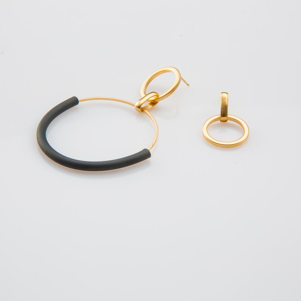 תמונת מוצר, עגילים א-סימטריים, בצבע זהב עגיל אחד גדול עם סיליקון שחור, והשני קטן. שניהם בנויים מחוליות עגולות בגדלים שונים.