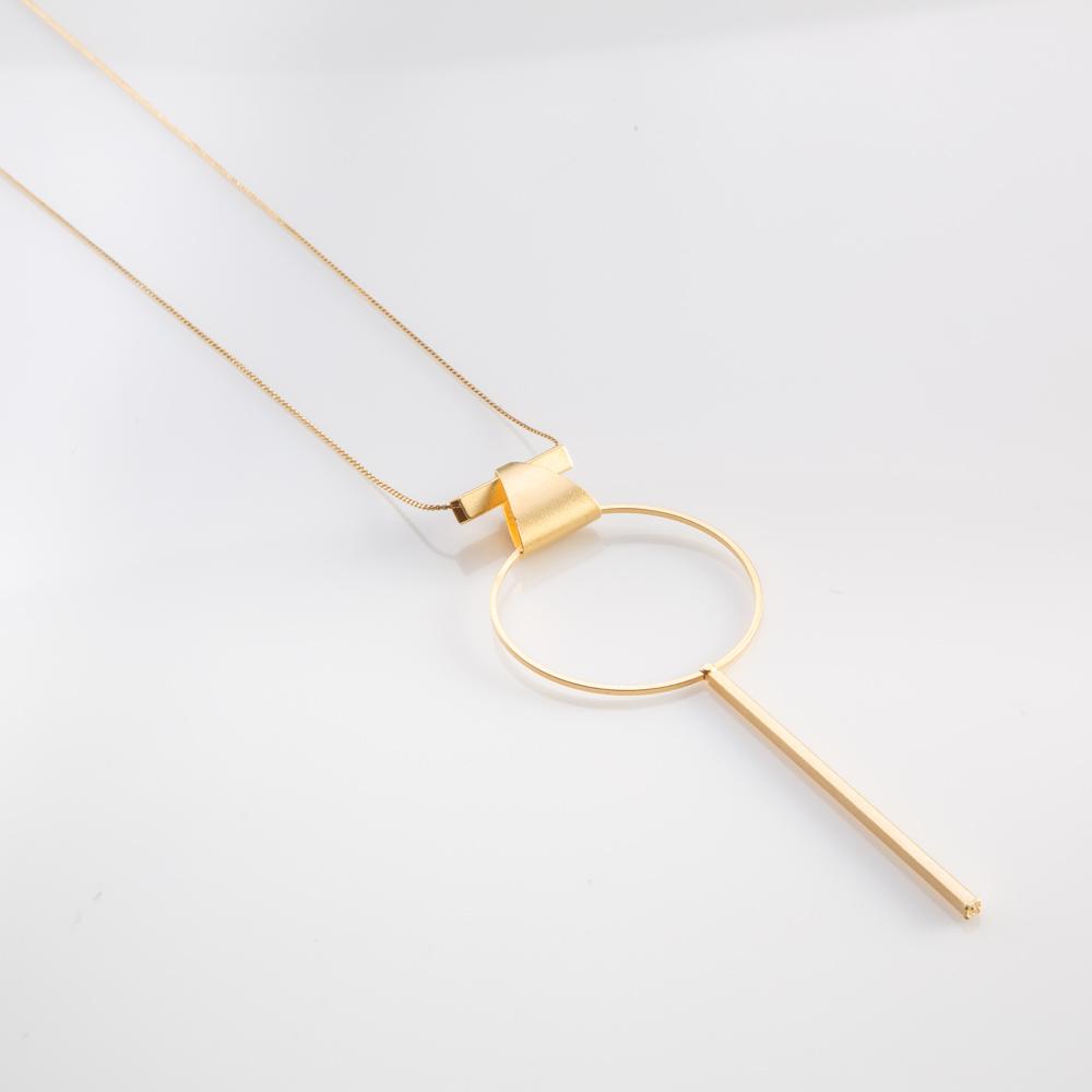 תמונת מוצר, שרשרת ארוכה ודקה, בצבע זהב, עם תליון גדול ועדין הבנוי מאלמנטים גאומטריים: משולש, עיגול ומקל.