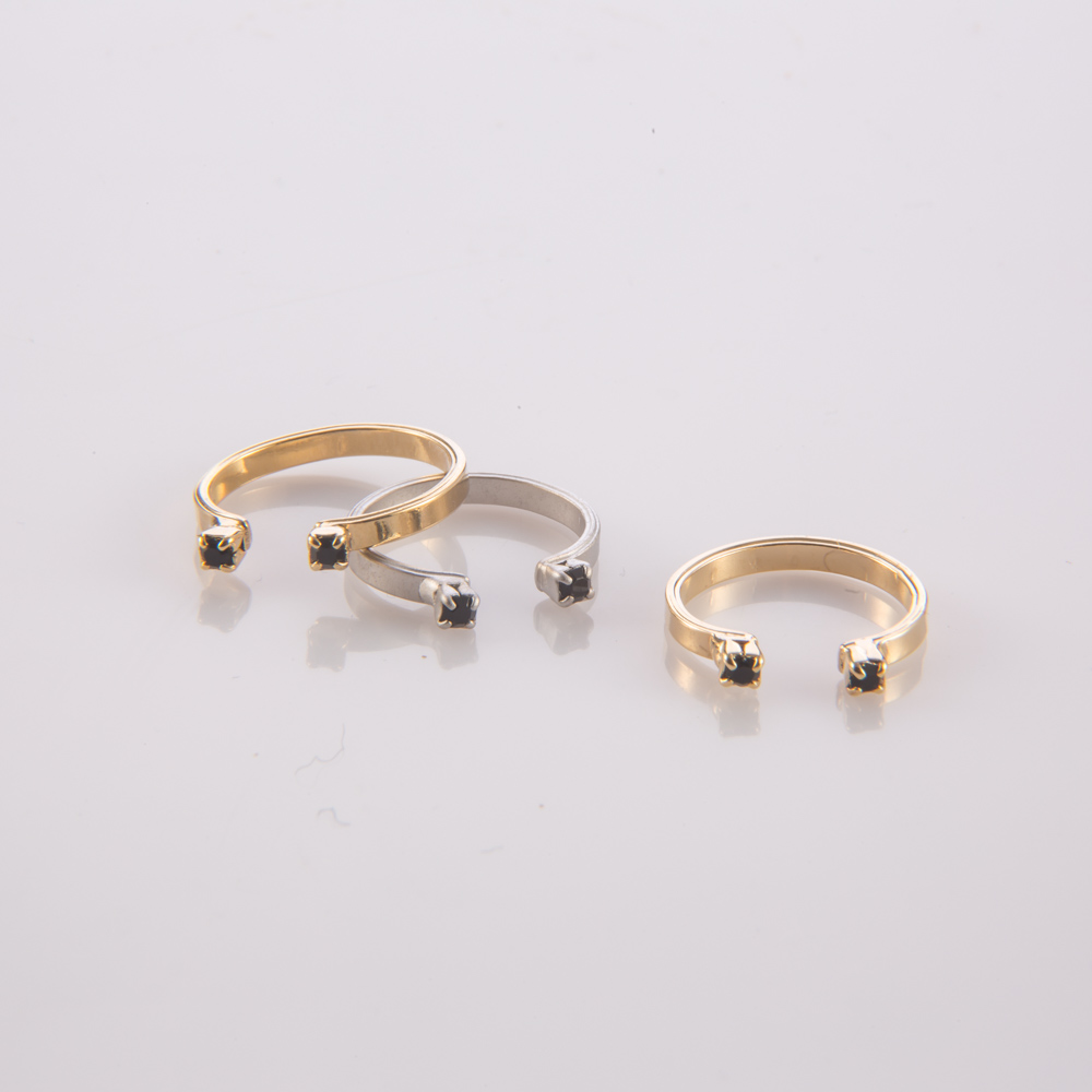 תמונת מוצר, טבעת קטנה פתוחה, משובצת שתי אבנים קטנות בצבע שחור בקצה כל צד. בתמונה מוצגת גם בצבע כסף וגם בצבע זהב.