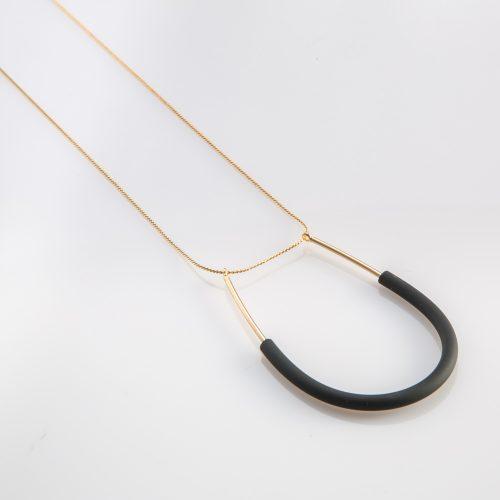 תמונת מוצר, שרשרת דקה וארוכה בצבע זהב, עם תליון דק בצורת פרסה ארוכה עם צינור סיליקון שחור דק בחציו.