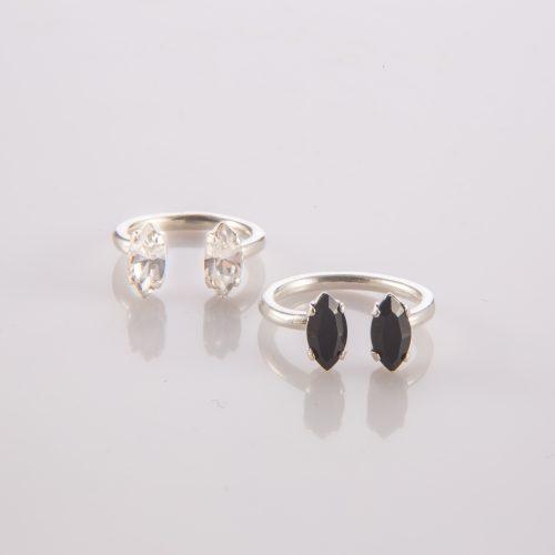 תמונת מוצר, טבעת מכסף פתוחה עם שתי אבנים אובליות בקצוות. בתמונה מוצגות שתי טבעות את עם אבנים שחורות ואחת עם אבנים שקופות.