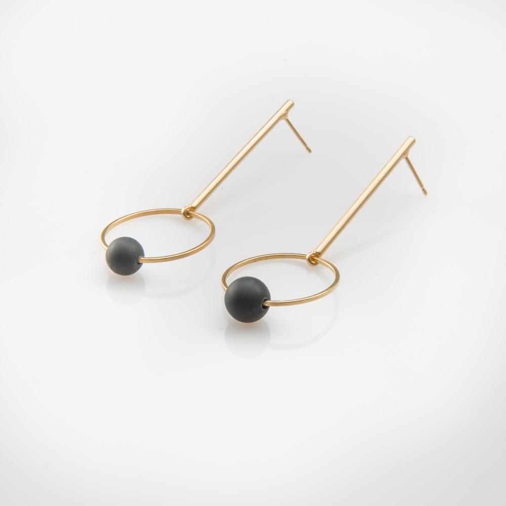 תמונת מוצר, עגילים ארוכים בצבע זהב הבנויים ממוט ארך עם חוליה עגולה בקצה וחרוז סיליקון שחור באמצע.