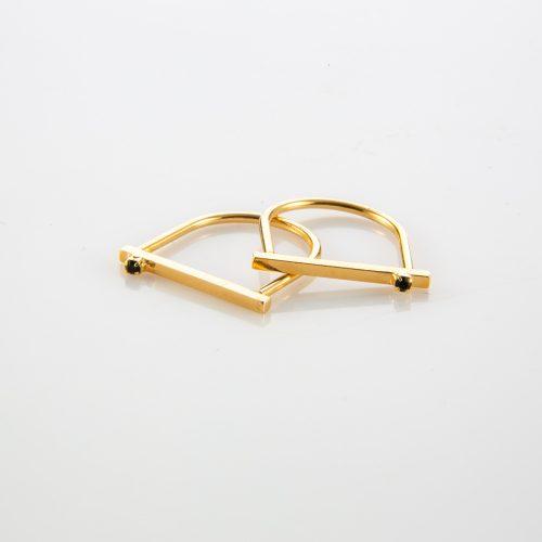 תמונת מוצר,טבעת דקה בצבע זהב, חלקה העליון שטוח ומשובץ באבן שחורה קטנה.