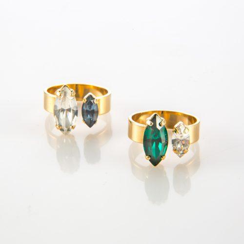 תמונת מוצר, טבעת עם בסיס עבה בצבע זהב, בשיבוץ שתי אבנים גדולות אובליות בצבעים וגדלים שונים. בתמונה מוצגות שתי טבעות האחת עם אבן ירוקה ואבן שקופה והשניה עם אבן שקופה ואבן כחולה.