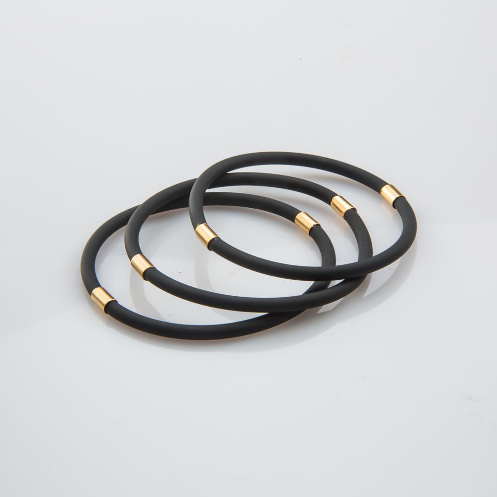 תמונת מוצר, שלושה צמידי סיליקון דקים בצבע שחור עם שתי צינוריות מתכת קצרות בצבע זהב.