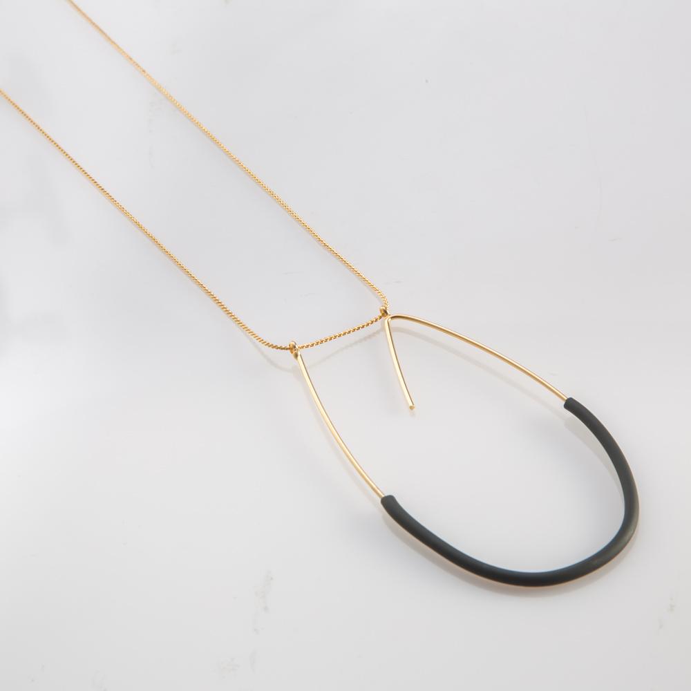 תמונת מוצר, שרשרת ארוכה ודקה בצבע זהב עם תליון גדול ודק בצורת האות ט, בשילוב צינור סיליקון שחור.