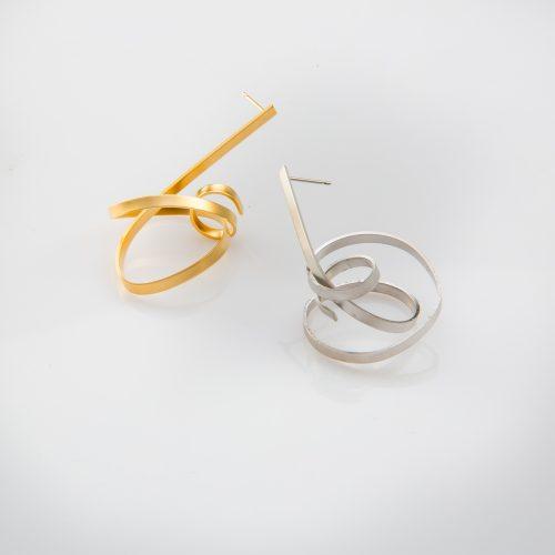 תמונת מוצר, עגיל בודד גדול הבנוי ממוט שטוח המכופף לשבלול בעבודת יד חופשית. בתמונה מופיע גם בצבע זהב וגם בצבע כסף.