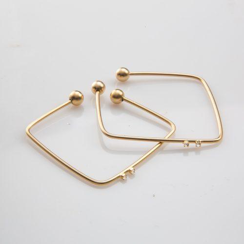 תמונת מוצר, צמיד דק פתוח, מרובע בצבע זהב עם שני כדורים בקצה ומשובץ שתי אבנים קטנות שקופות.