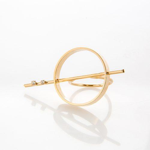 תמונת מוצר, טבעת בצבע זהב, עם מסגרת עיגול גדולה ומוט החוצה אותה ומשובץ בשתי אבנים קטנות בצבע קריסטל.