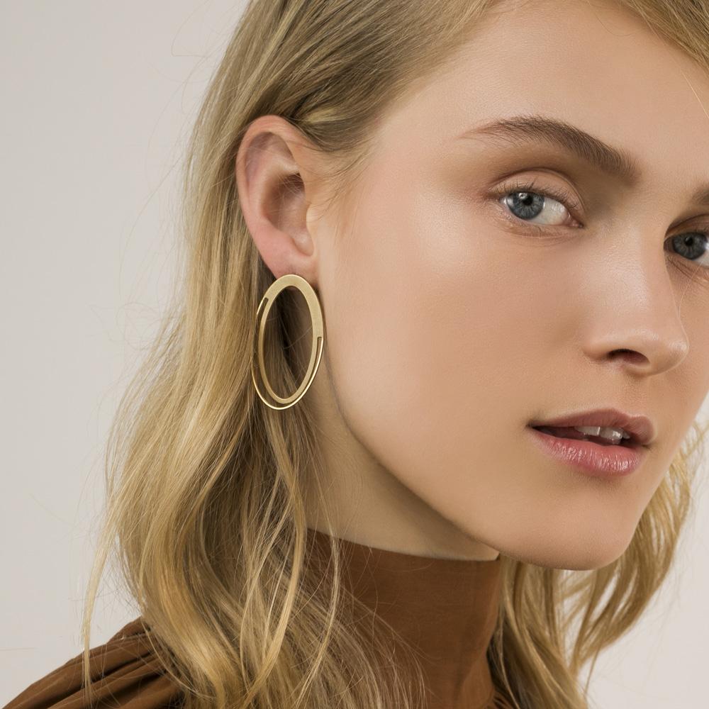 תמונה על דוגמנית, עגילי אליפסה גדולים שטוחים וחלולים. בצבע זהב.