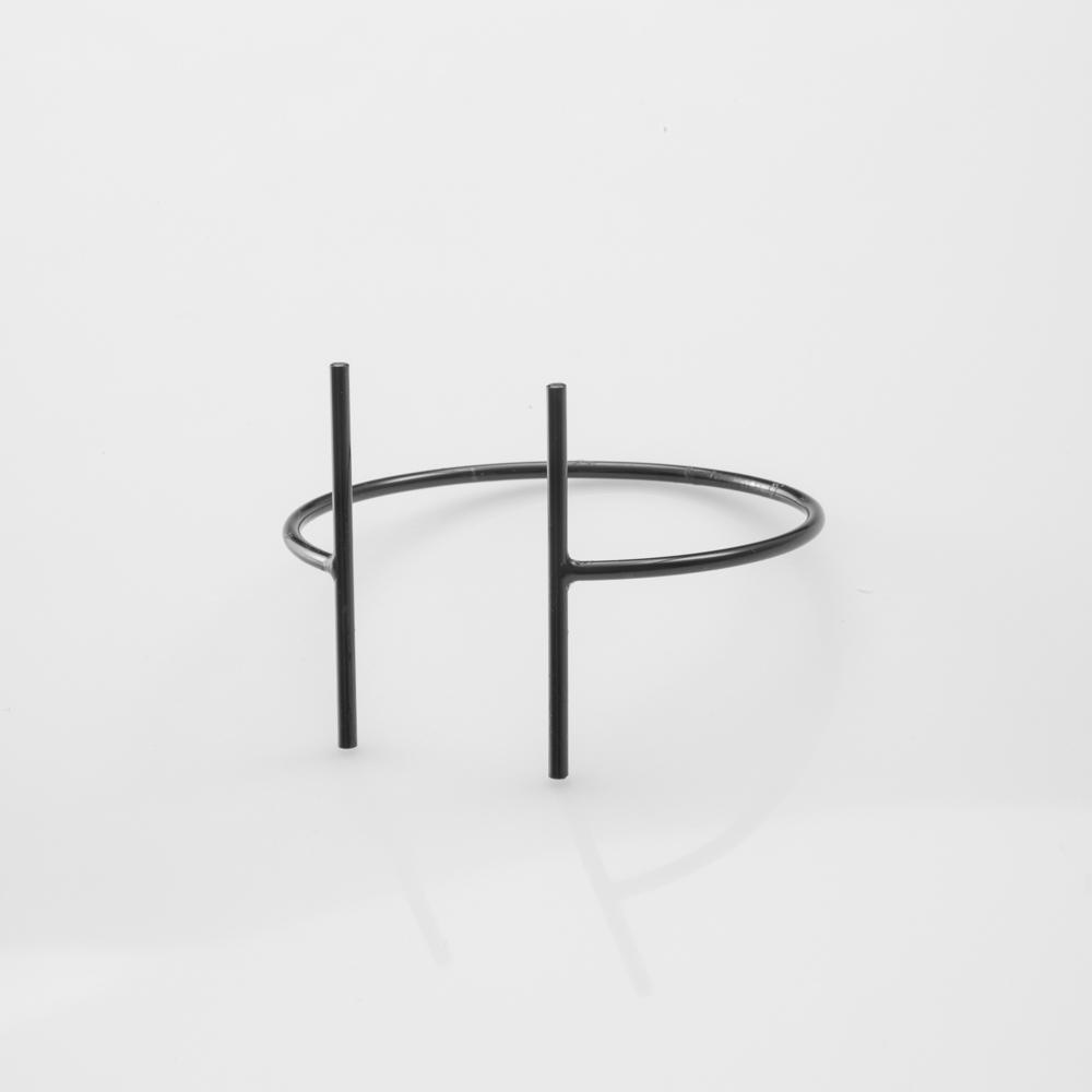 תמונת מוצר, צמיד דק פתוח בצבע שחור, עם שני מוטות ארוכים ודקים בקצוות.