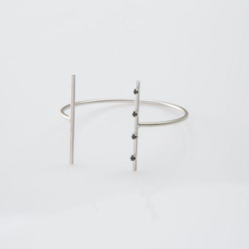 תמונת מוצר, צמיד פתוח בצבע כסף עם שני מוטות ארוכים ודקים בשיבוץ ארבע אבנים קטנות שחורות.