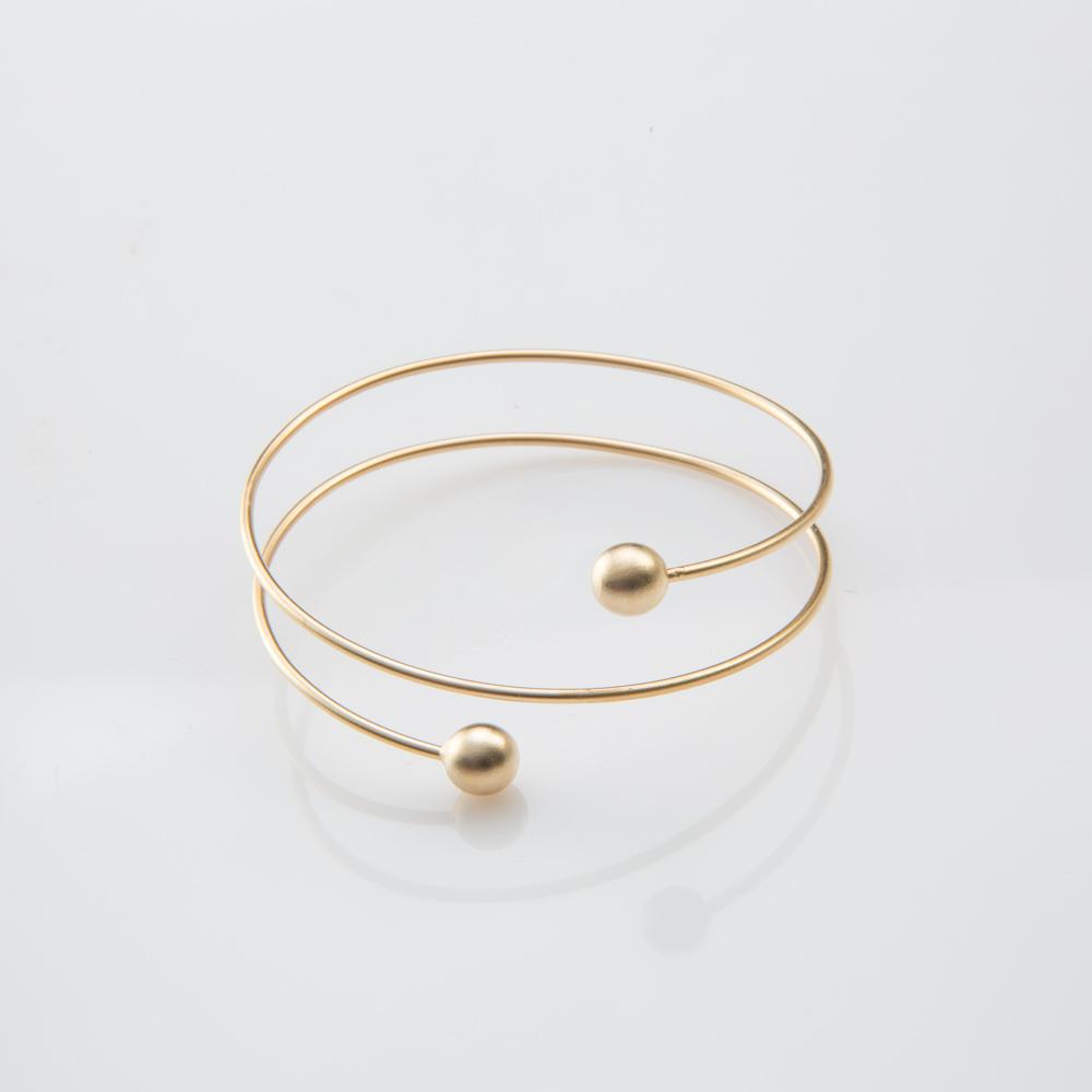 תמונת מוצר, צמיד בצבע זהב בצורת ספירלה, עם כדור בכל קצה.