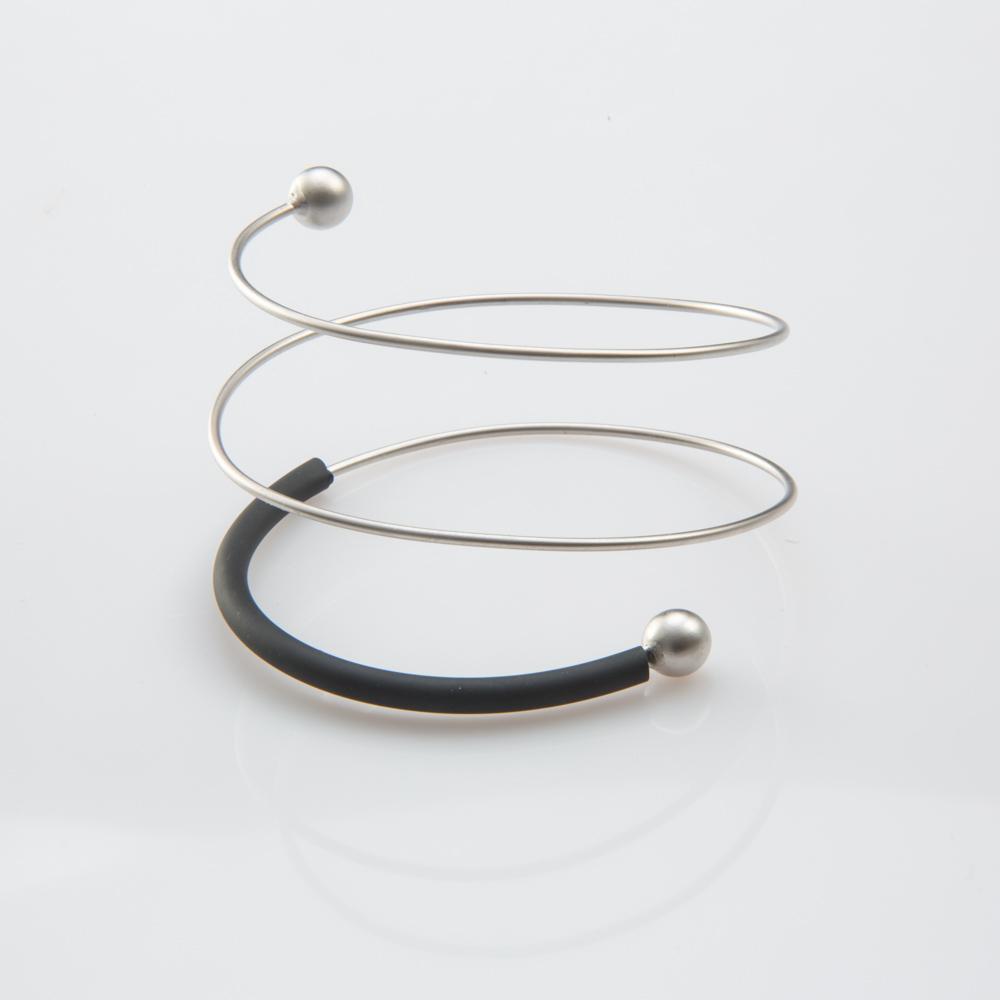 תמונת מוצר, צמיד ספירלה בצבע כסף עם צינור סילקון שחור בחלקו וכדרים בקצוות.