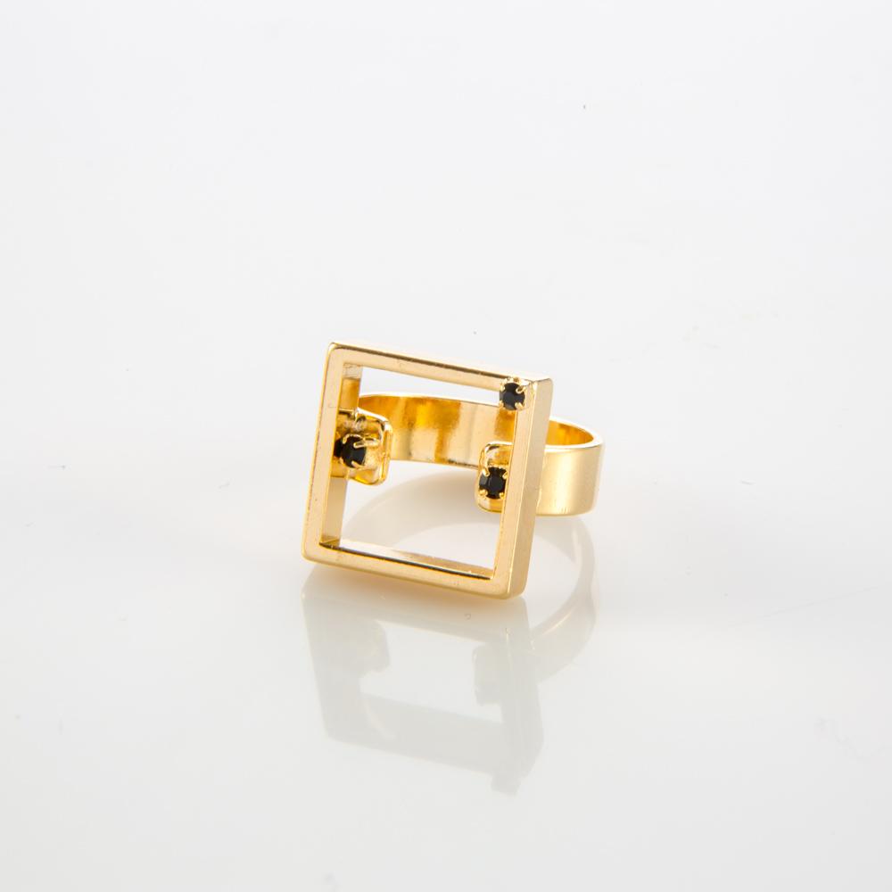 תמונת מוצר, טבעת בצבע זהב, עם בסיס רחב ומסגרת ריבוע במרכז. בתוכה משובצות שתי אבנים שחורות קטנות ואבן שחורה קטנה נוספת משובצת על המסגרת.
