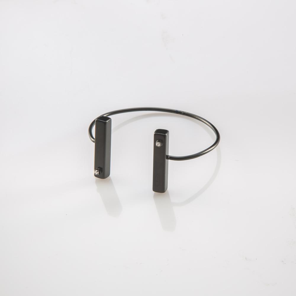 תמונת מוצר, צמיד פתוח בצבי שחור עם שני צינורות מרובעים ורחבים בקצוות משובצים בשתי אבנים קטנות שקופות.