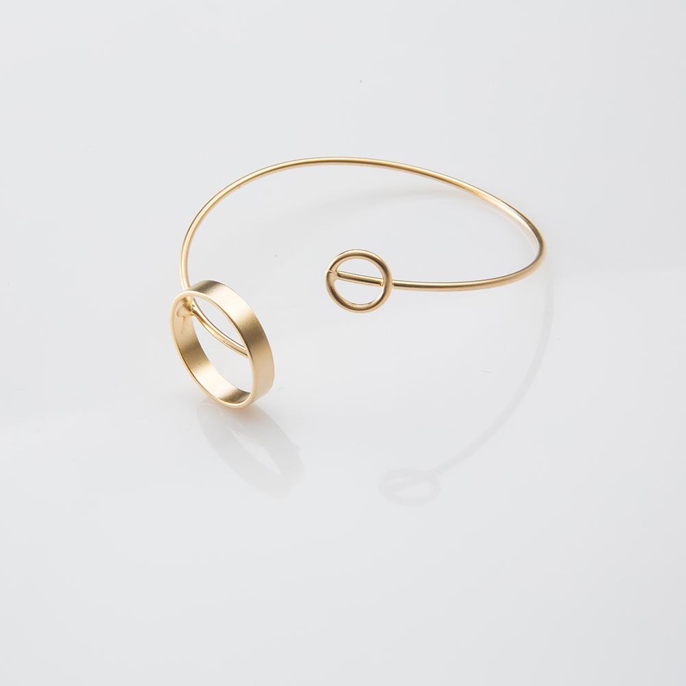 תמונת מוצר, צמיד מלופף בצבע זהב עם עיגול גדול ועיגול קטן בקצה.