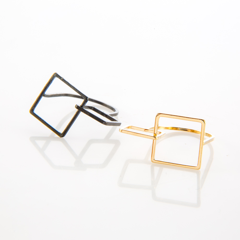 תמונת מוצר, טבעת שכולה בקווי מתאר דקים, בחלק העליון שלה שני ריבועים בגדלים שונים. בתמונה מופיעה בצבע זהב ובצבע שחור.