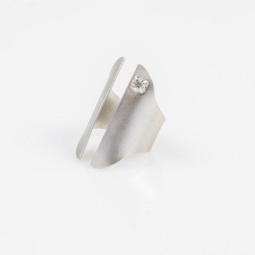 תמונת מוצר, טבעת עבה בצבע כסף, בשיבוץ אבן קריסטל קטנה.