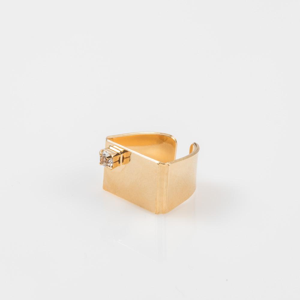תמונת מוצר, טבעת מלבנית עבה בצבע זהב, בשיבוץ אבן קריסטל קטנה.