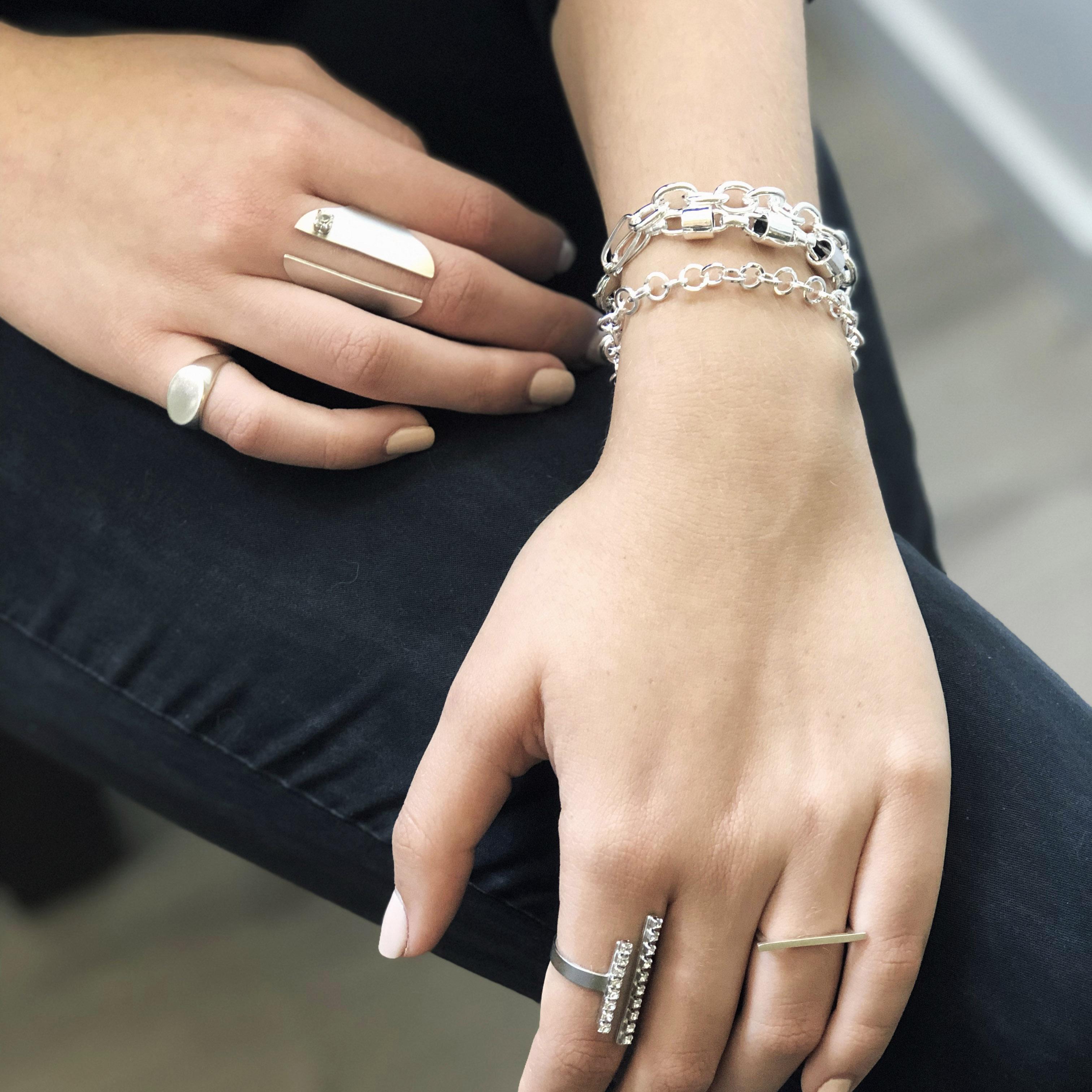 תמונה על דוגמנית, שלושה צמידי חוליות בצבע כסף. טבעת גדולה לאורך האצבע בצבע כסף בשיבוץ אבן קריסטל קטנה, טבעת חותם בצבע כסף. טבעת פתוחה בצבע כסף עם שני מקלות לאורך משובצים באבני קריסטל קטנות. טבעת כסף דקה מקל לרוחב.